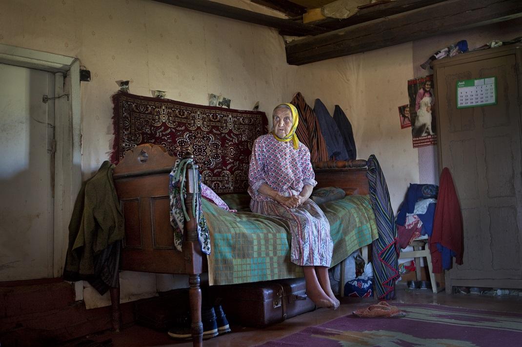 ηλικιωμένη γυναίκα κάθεται σε κρεβάτι
