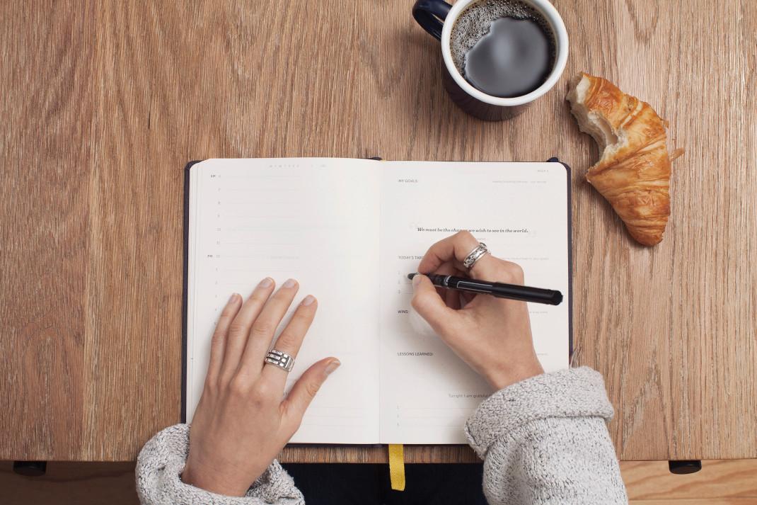 γυναίκα γράφει σε σημειωματάριο με καφέ και κρουασάν