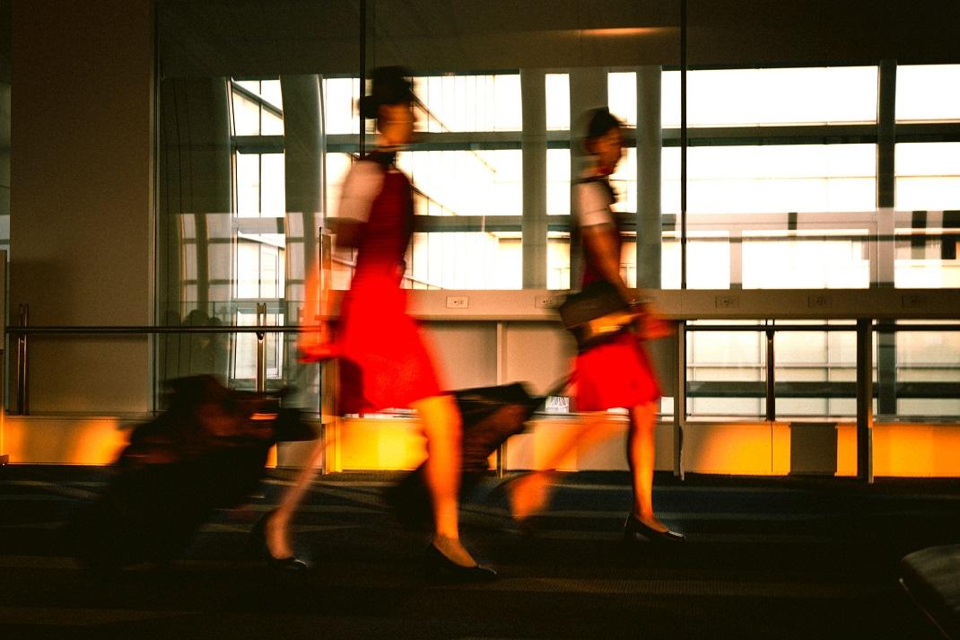 Δύο αεροσυνοδοί με κόκκινες στολές κρατούν βαλίτσες στο χέρι
