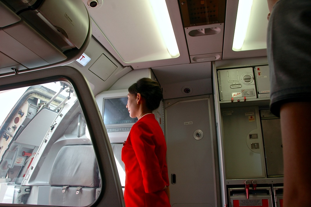 Αεροσυνοδός με κόκκινη στολή στην πόρτα του αεροπλάνου