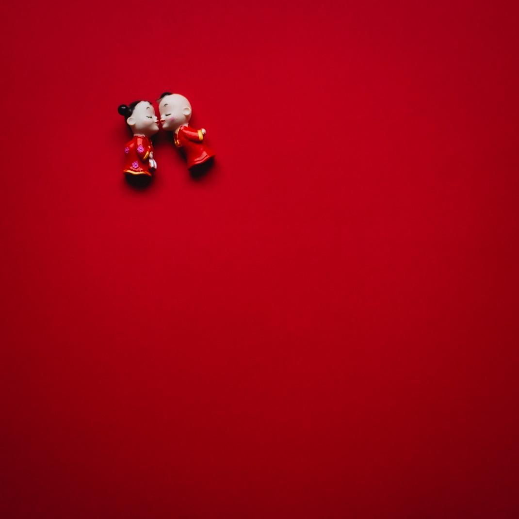 Δύο φιγούρες φιλιούνται σε κόκκινο φόντο