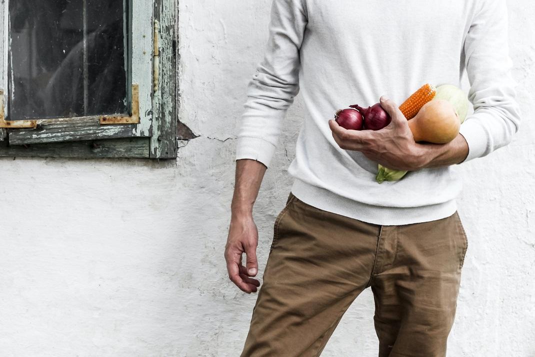 άνδρας που κάνει δίαιτα κρατά λαχανικά