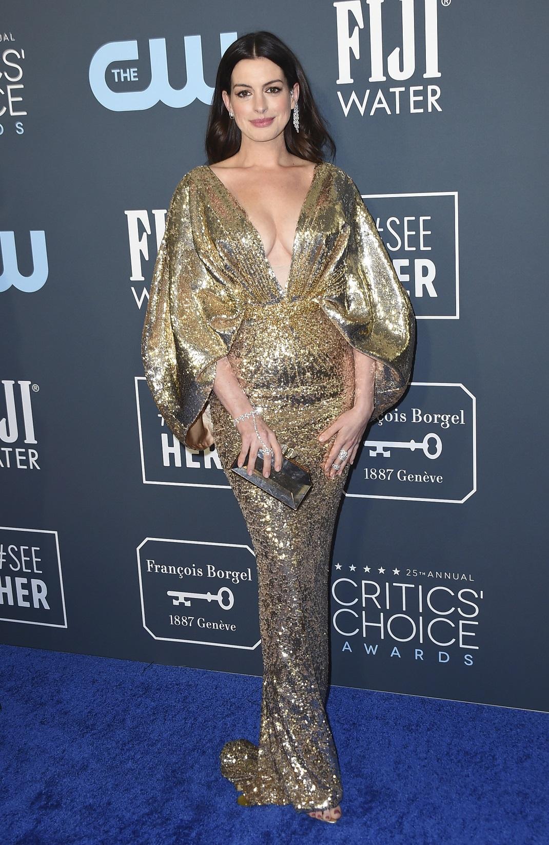 Η Αν Χάθαγουεϊ με χρυσό φόρεμα κρατά χρυσή τσάντα
