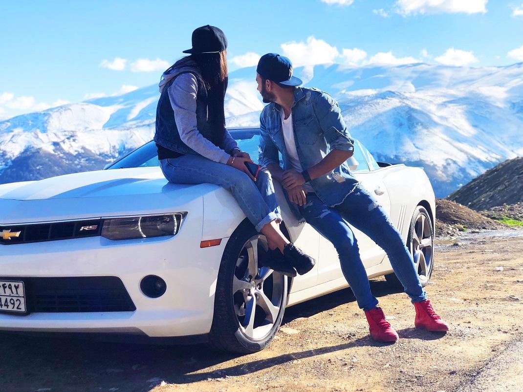 Άνδρας με τζιν παντελόνι και γυναίκα κάθεται πάνω σε λευκό αυτοκίνητο