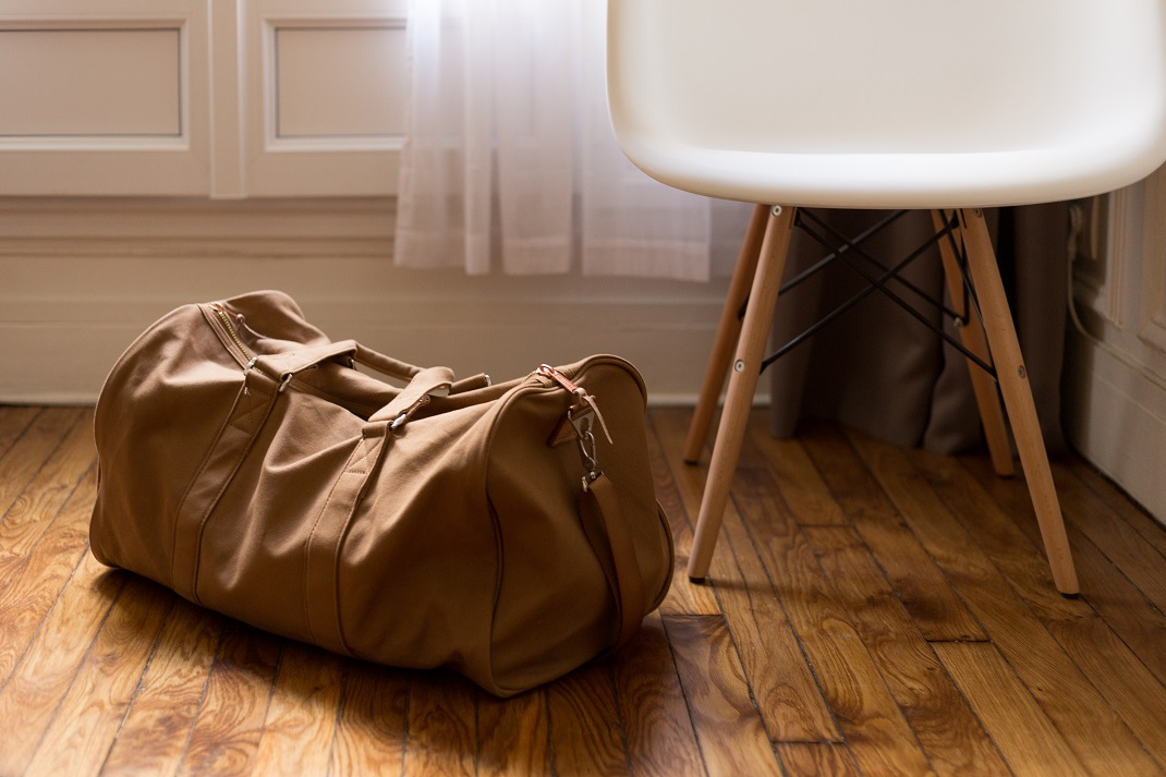 Σακ βουαγιάζ γεμάτο δίπλα σε καρέκλα