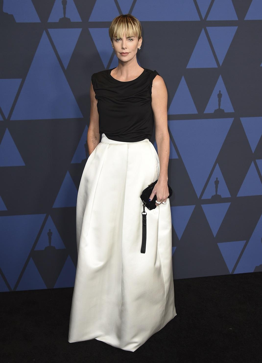 Η Σαρλίζ Θερόν με ασπρόμαυρο φόρεμα και μαύρο τσαντάκι