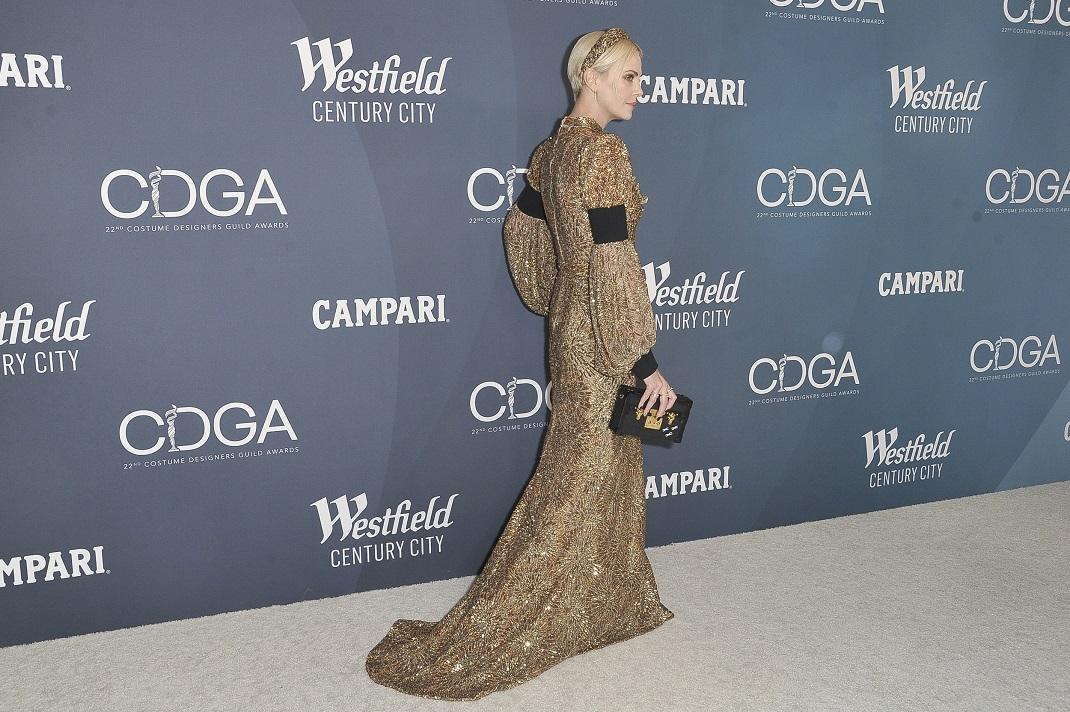 Η Σαρλίζ Θερόν με χρυσό φόρεμα και μαύρο τσαντάκι