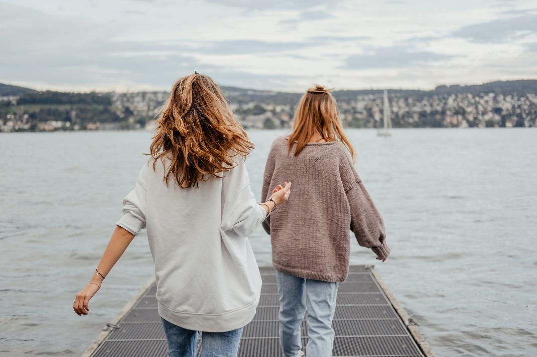 Δύο αληθινές φίλες περπατούν στη θάλασσα