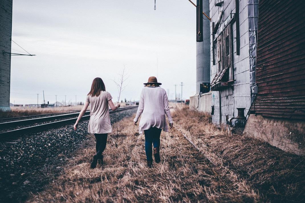 Δύο φίλες περπατούν δίπλα από τις ράγες του τρένου