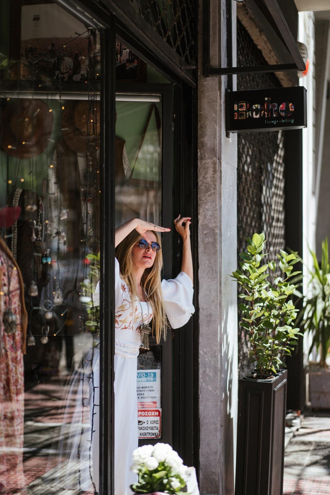 Η Τζούλη Αγοράκη με λευκό boho φόρεμα στο μαγαζί.