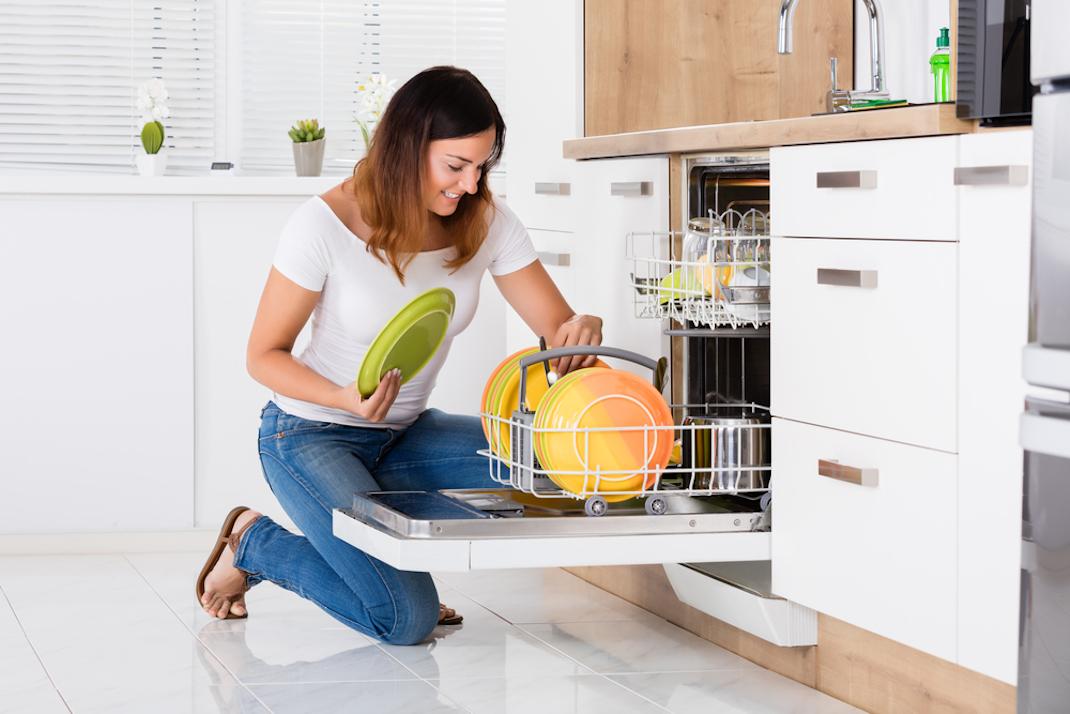Γυναίκα βάζει πιάτα σε πλυντήριο πιάτων