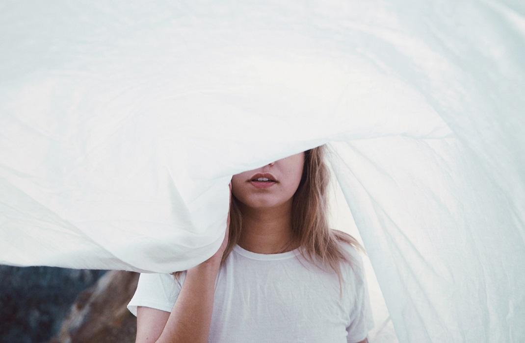 Γυναίκα φορά λευκό μπλουζάκι και κρύβεται πίσω από λευκό σεντόνι