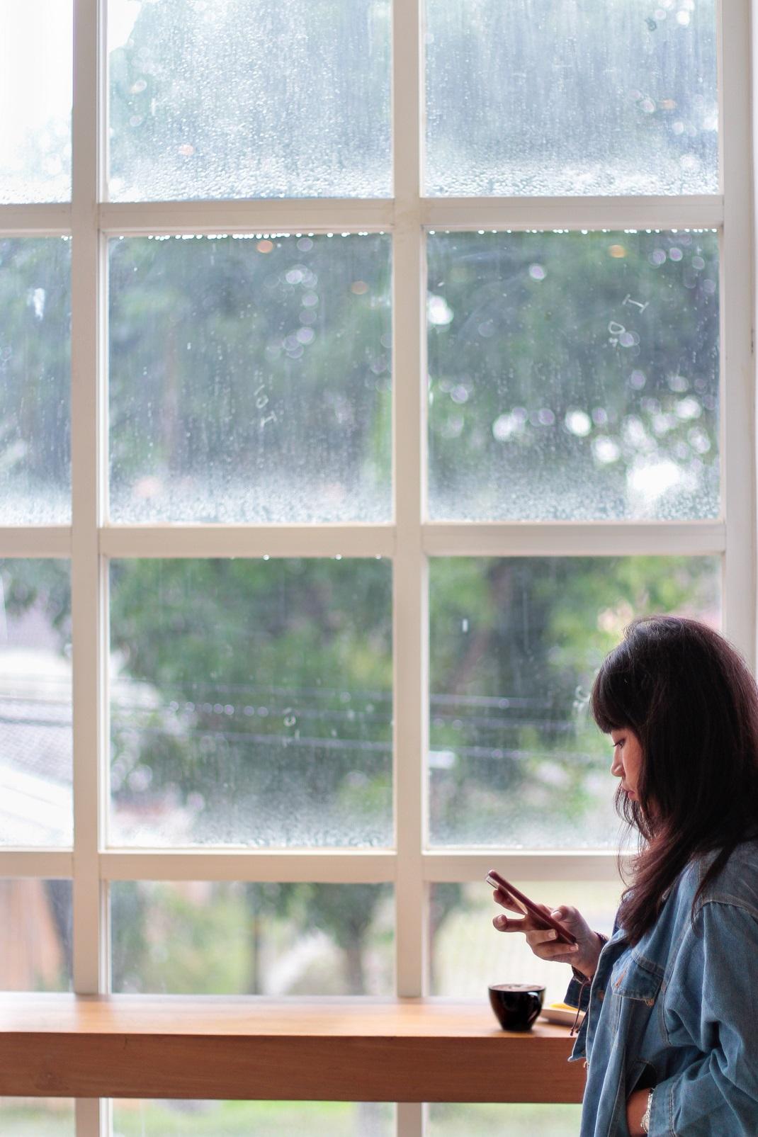 Γυναίκα στο παράθυρο κοιτάει το κινητό της