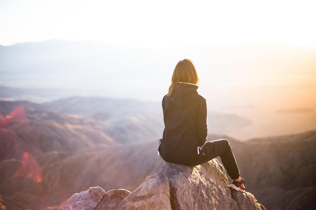 Γυναίκα που συγκρίνει τον εαυτό της με άλλους κάθεται στην κορυφή ενός βουνού