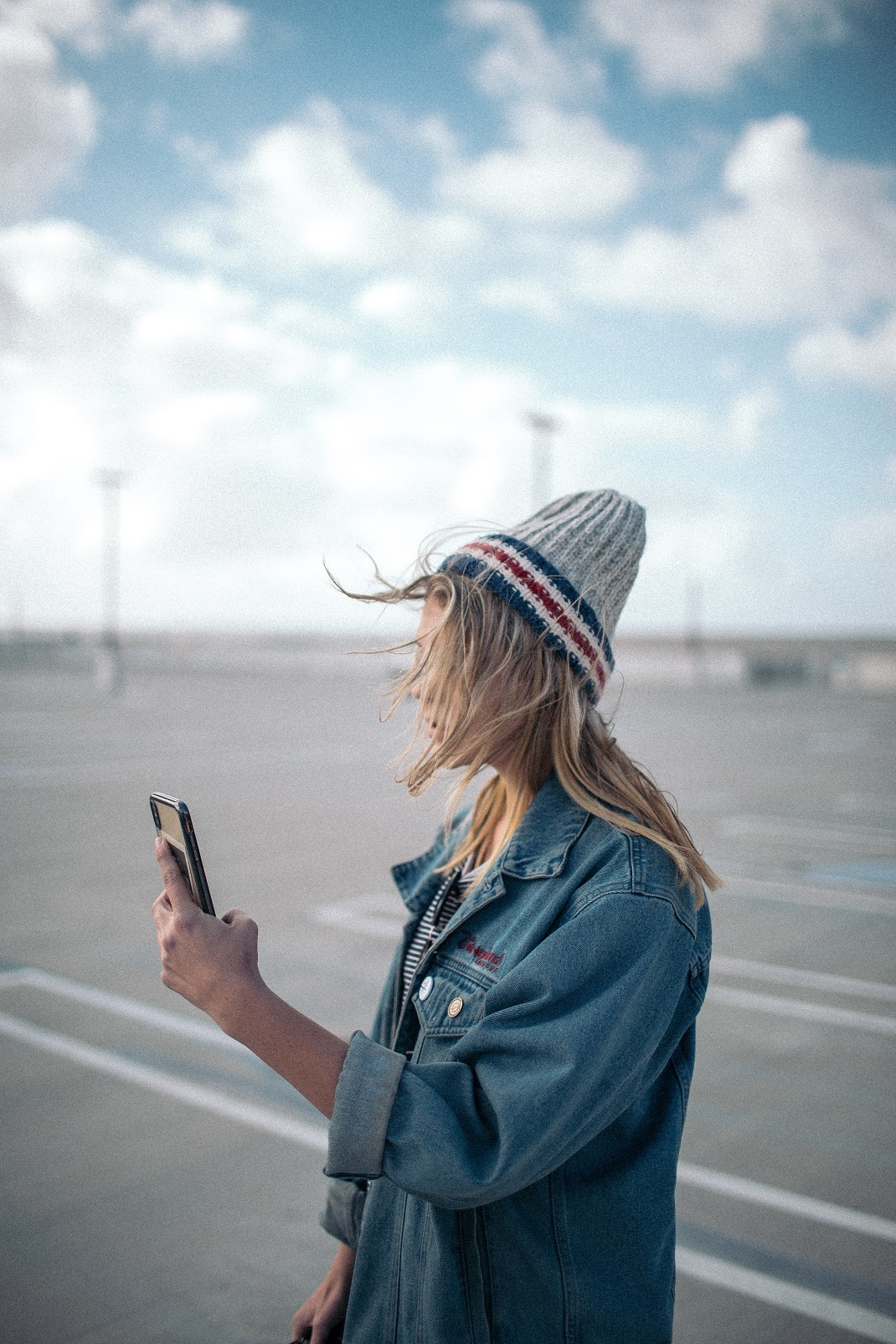 Γυναίκα με τζιν μπουφάν κοιτάει το κινητό της