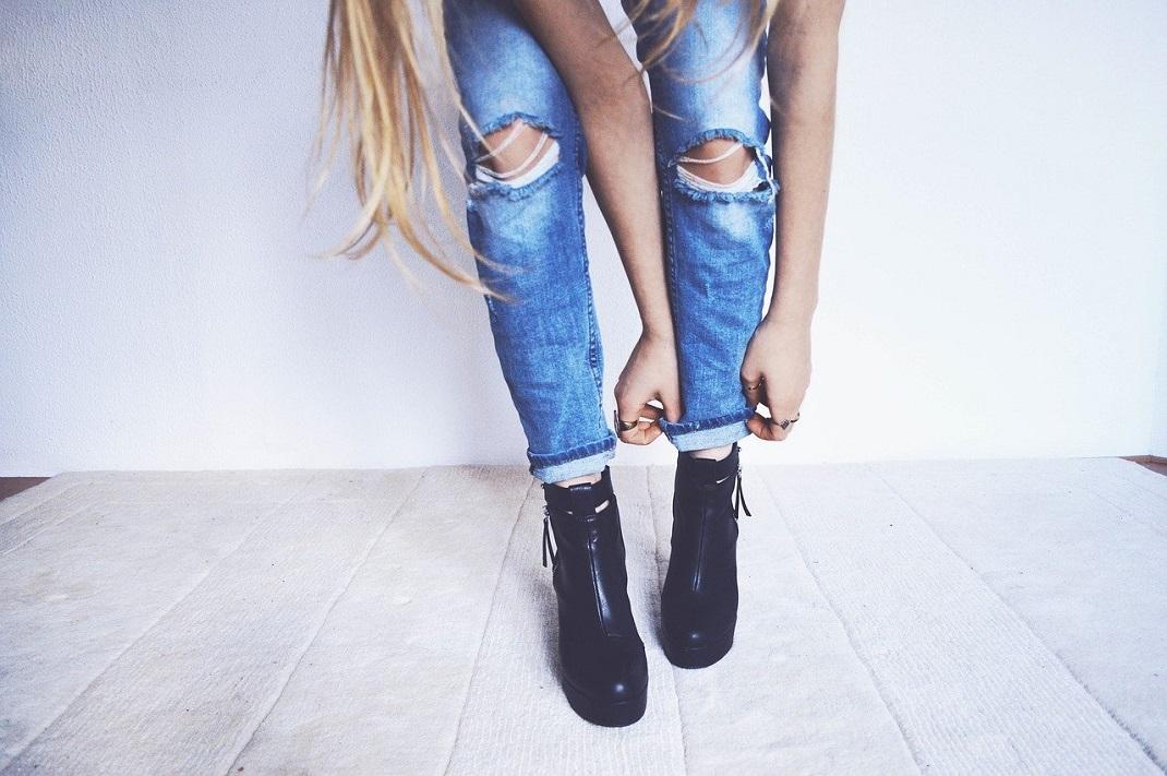 Γυναίκα με μποτάκια φορά τζιν παντελόνι