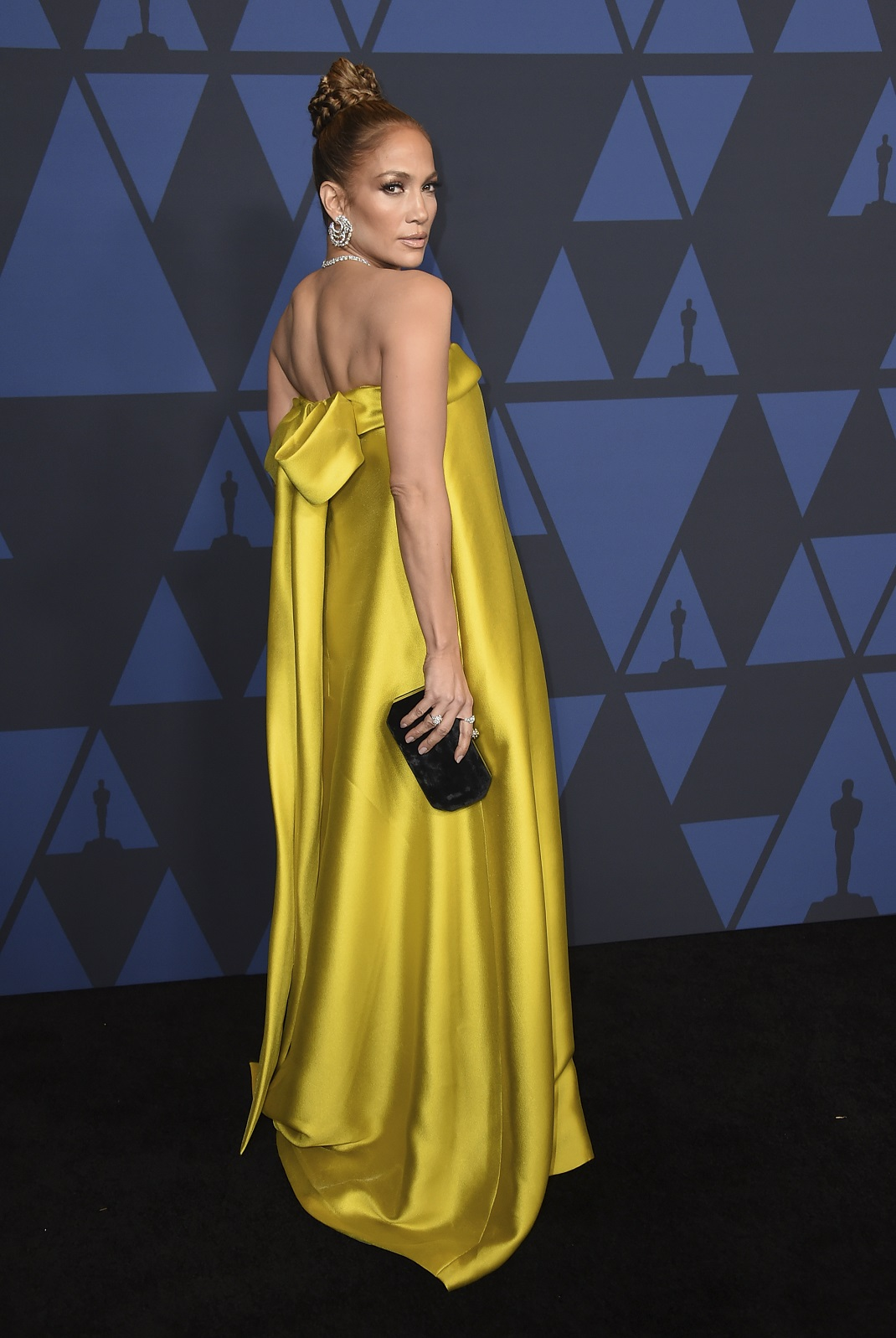 Η Τζάνιφερ Λόπεζ με χρυσό φόρεμα και μαύρο τσαντάκι