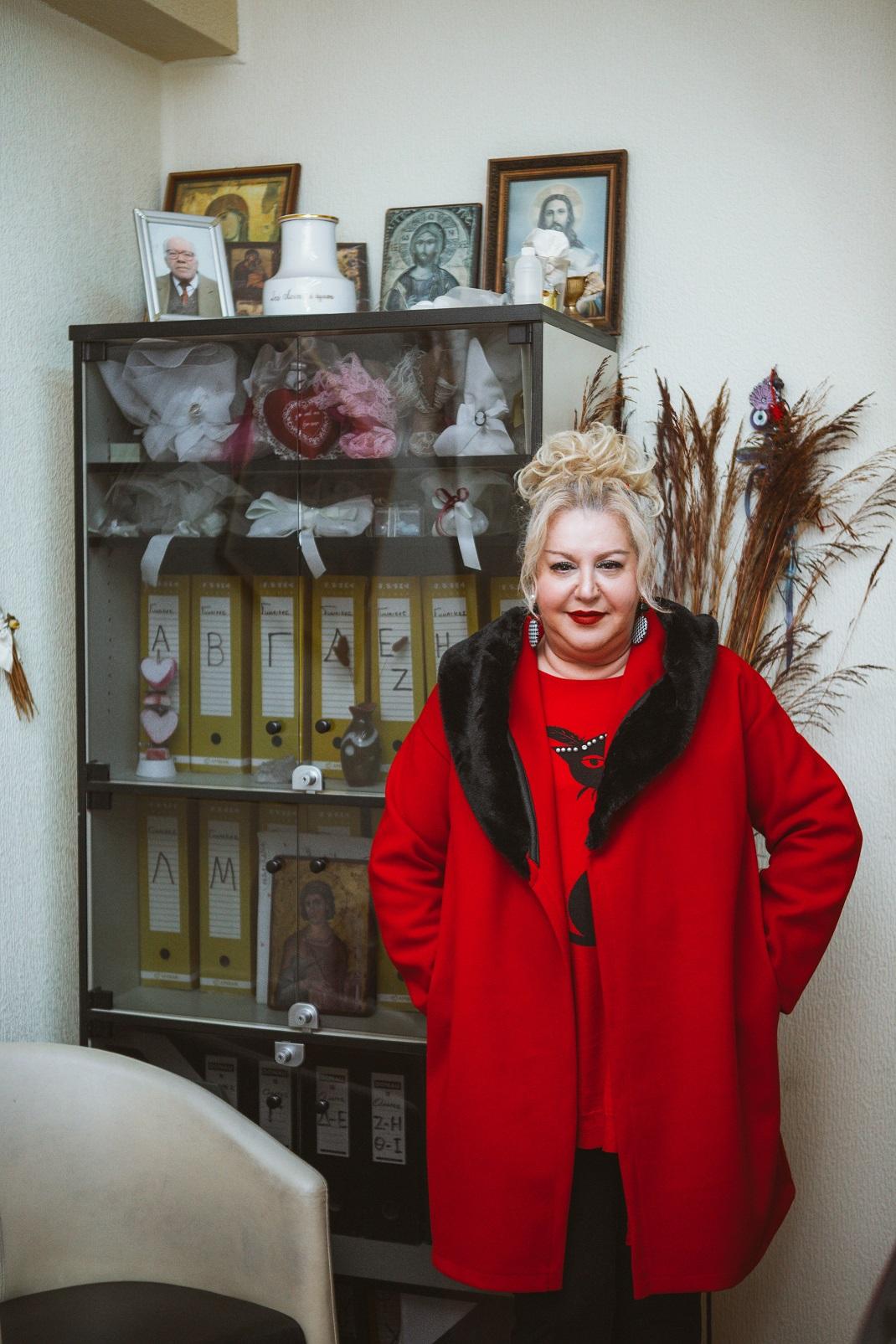 Η Κατερίνα Λούης με κόκκινο παλτό και τα χέρια στις τσέπες