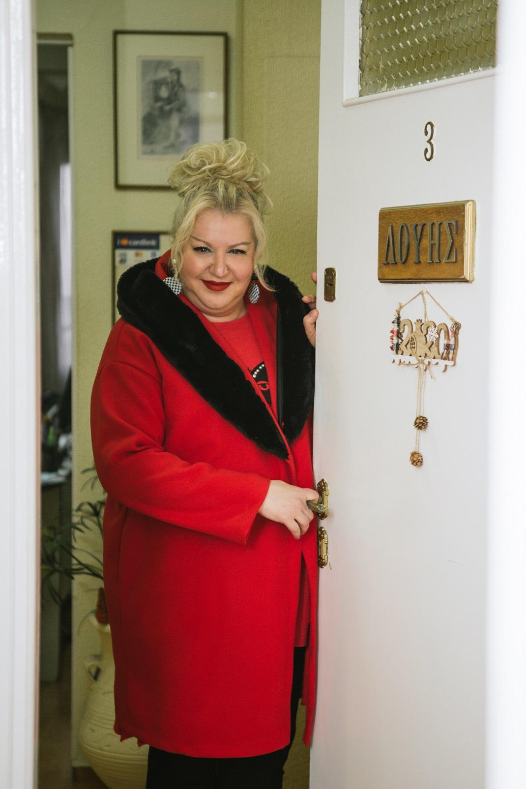 Η Κατερίνα Λούης φορά κόκκινο παλτό και ακουμπά την πόρτα