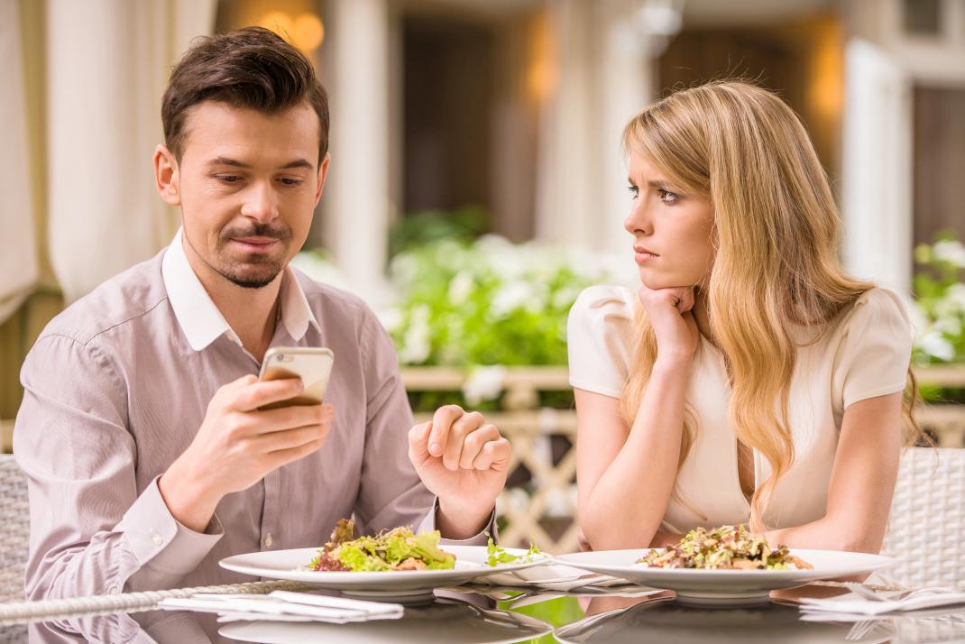 Ανδρας κοιτάει το κινητό του γιατί αισθάνεται άβολα με την συνοδό του