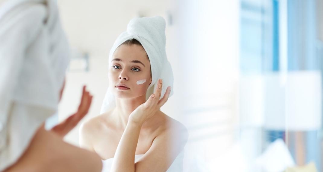 Γυναίκα κοιτάει το πρόσωπό της στον καθρέφτη/Photo:Shutterstock
