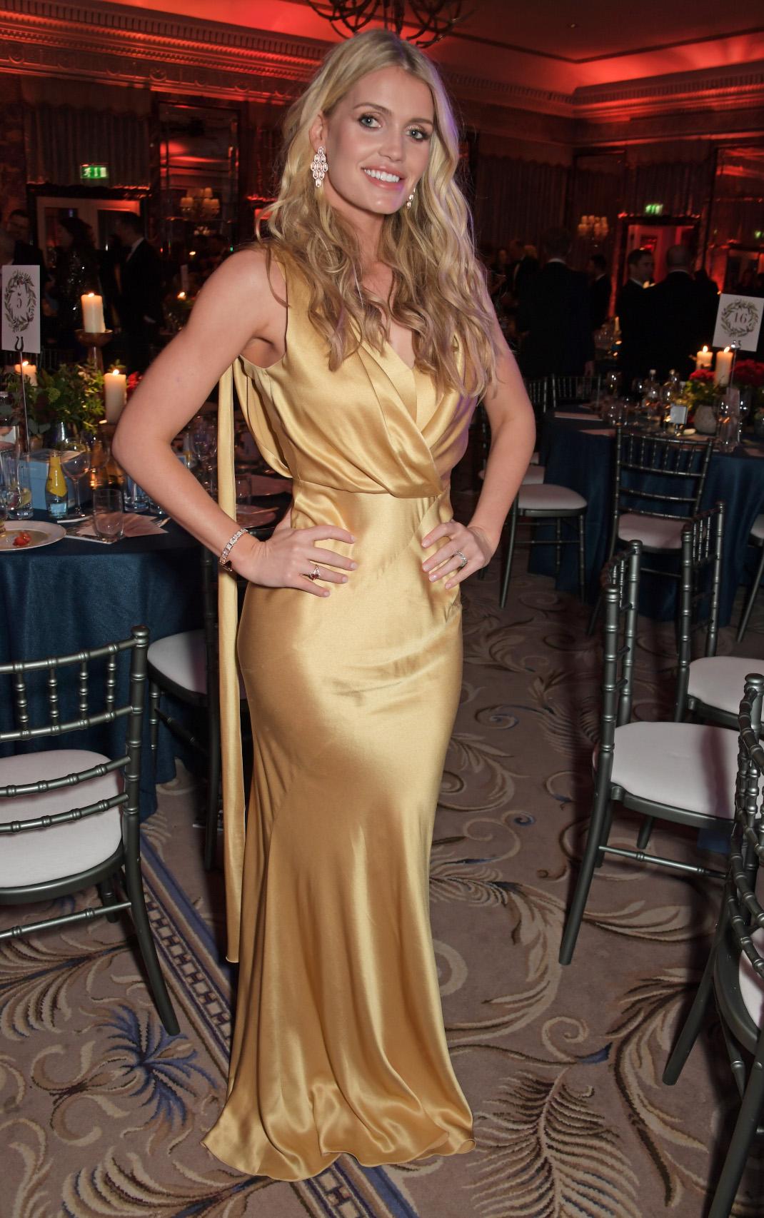 Η Λαίδη Κίττυ Σπένσερ με χρυσό φόρεμα χαμογελά