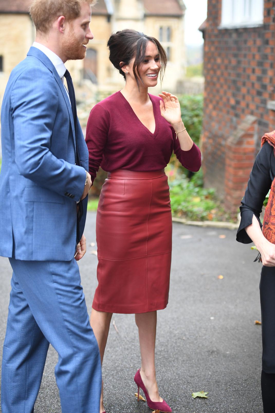Η Μέγκαν Μαρκλ με κόκκινη φούστα χαμογελάει