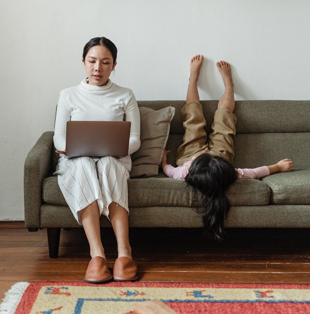 μητέρα με υπολογιστή και κορίτσάκι στον καναπέ sharenting