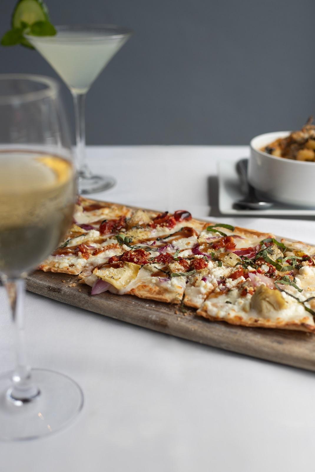 Πίτσα σε ξύλινο επιφάνεια με ποτήρι κρασί