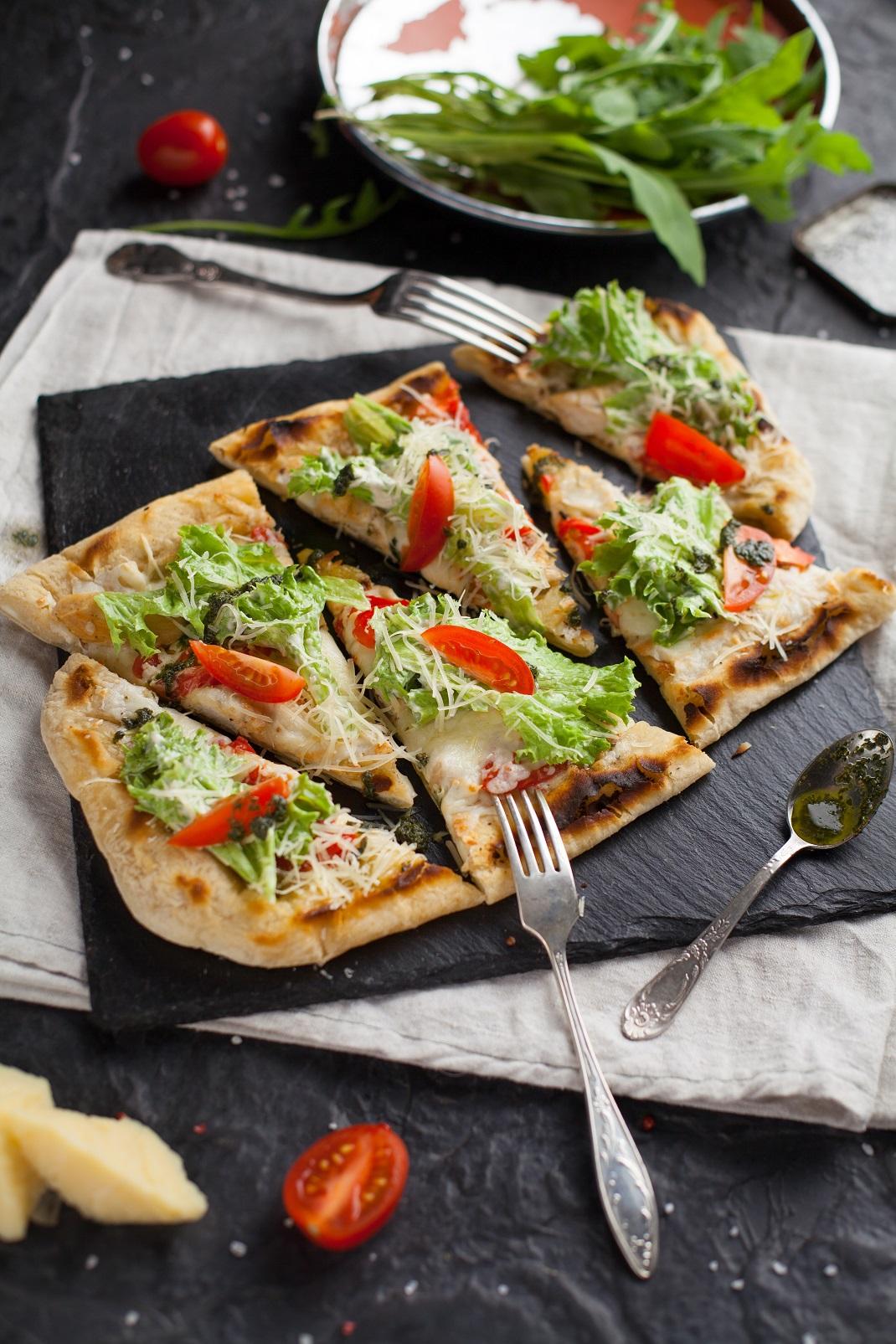 Πίτσα σε μαύρη ξύλινη επιφάνεις με κουτάλια και πιρούνια