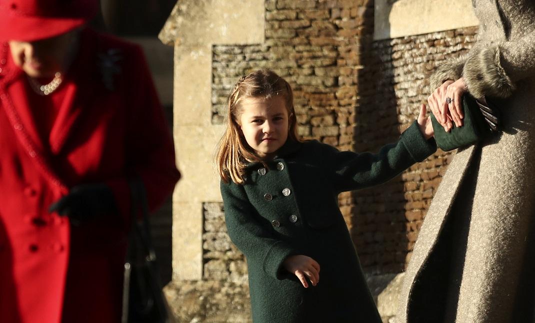 Η πριγκίπισσα Σάρλοτ με πράσινο παλτό κρατά το χέρι της Κέιτ Μίντλετον