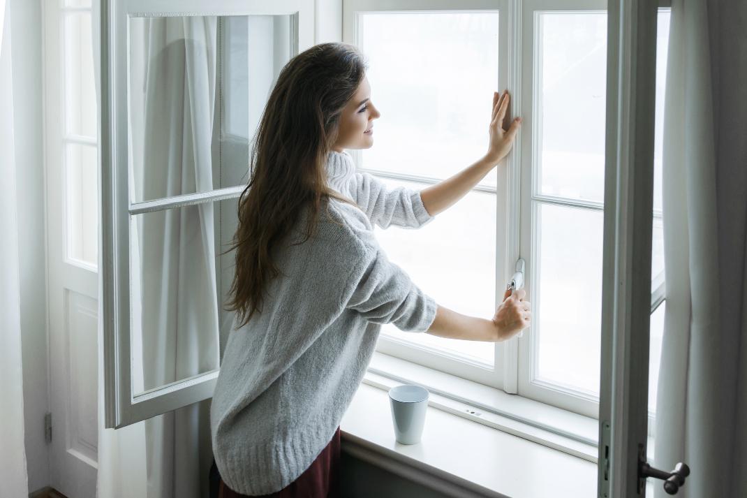 Γυναίκα κλείνει το παράθυρο για την προστασία των πνευμόνων