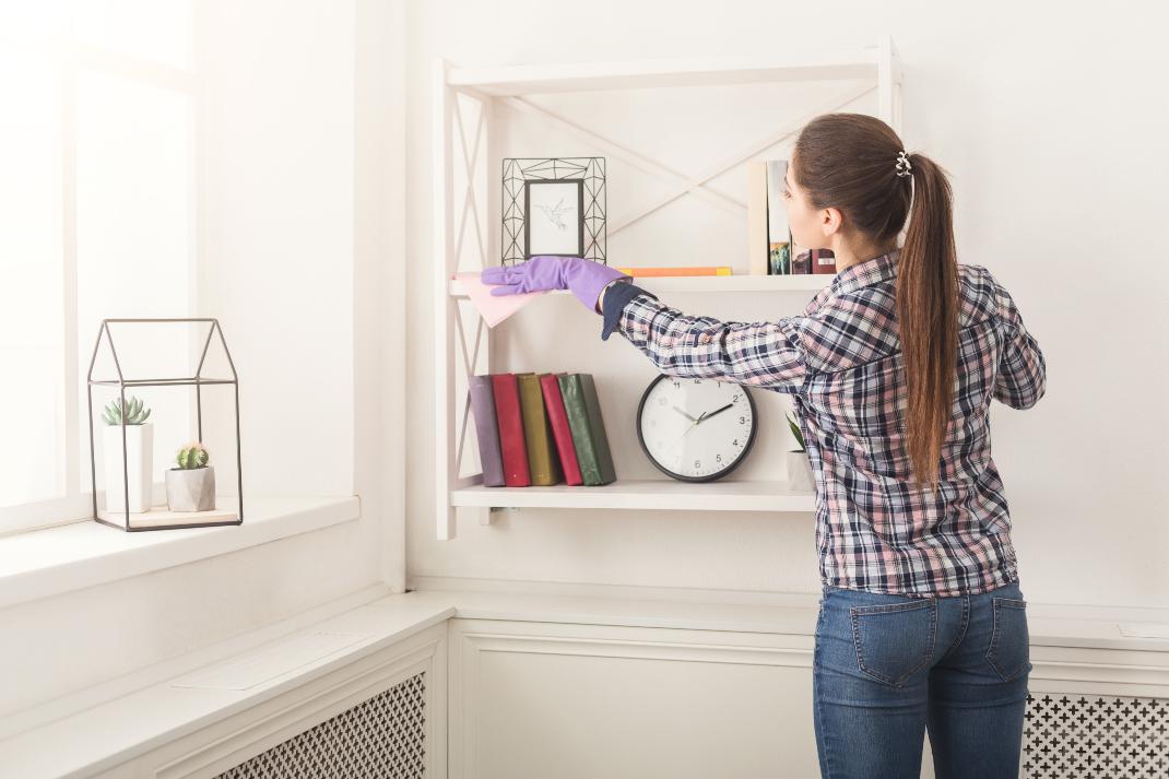 Γυναίκα ξεσκονίζει το ράφι της βιβλιοθήκης