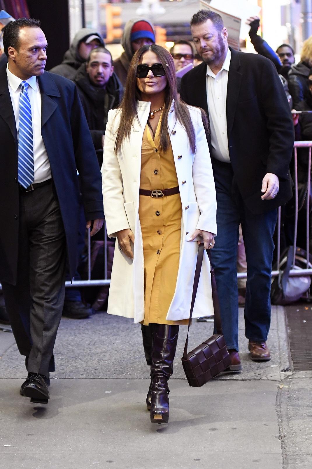 Η Σάλμα Χάγιεκ με μουσταρδί shirt dress και λευκό παλτό