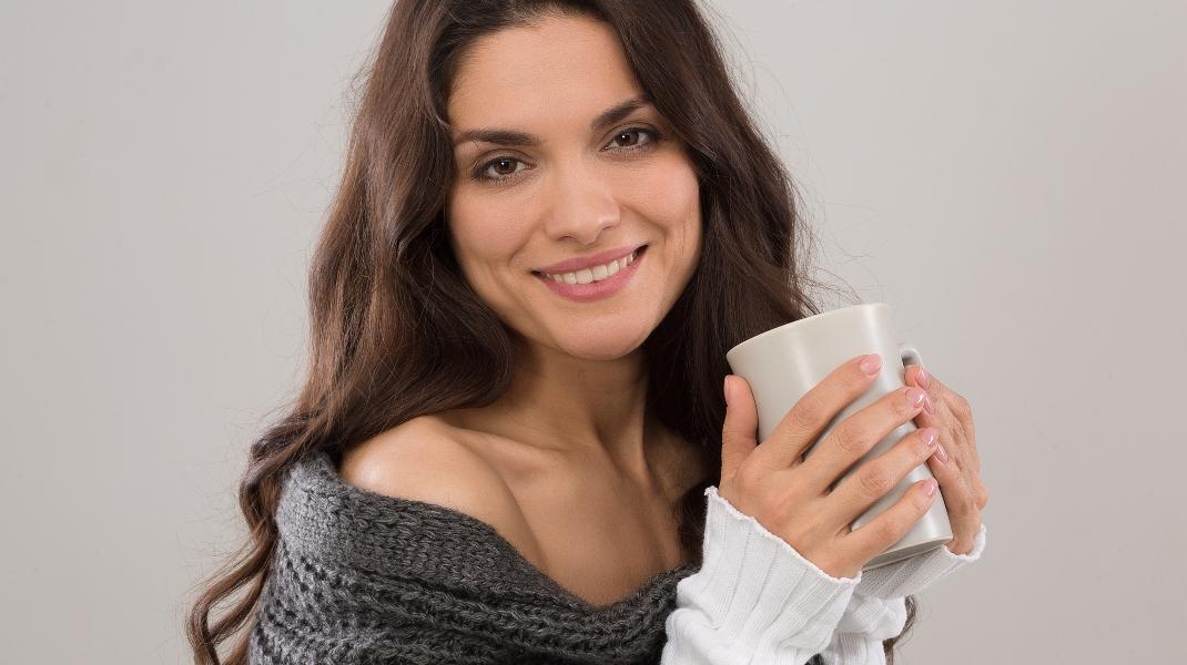 Χαμογελαστή γυναίκα, άνω των 40, πίνει καφέ/Photo:Shutterstock