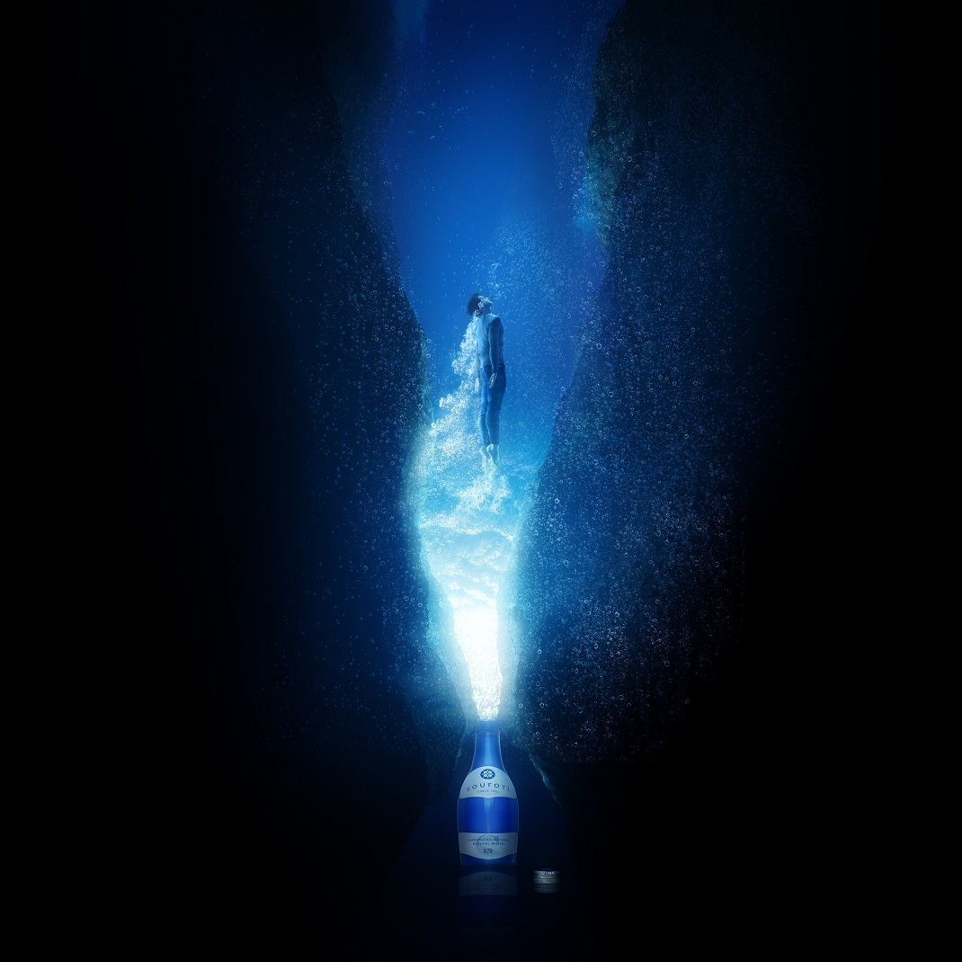 άνδρας κολυμπά και στο κάτω μέρος φαίνεται ένα μπουκάλι Souroti