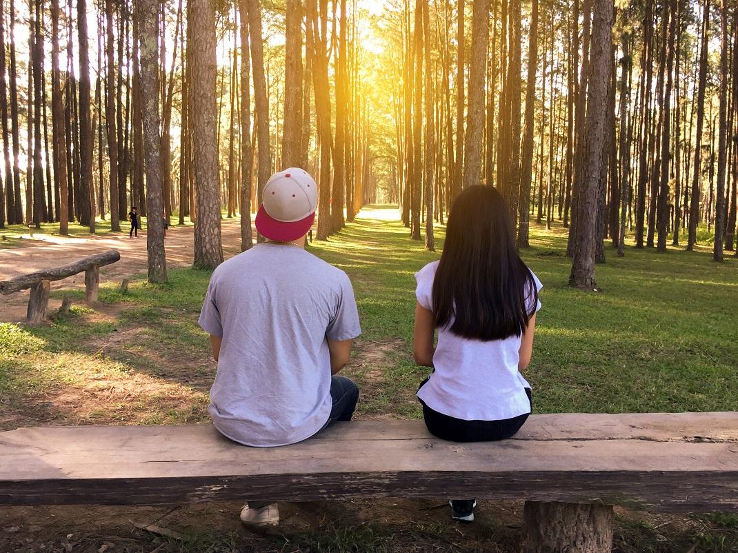 Ζευγάρι στο δάσος κάθεται σε παγκάκι