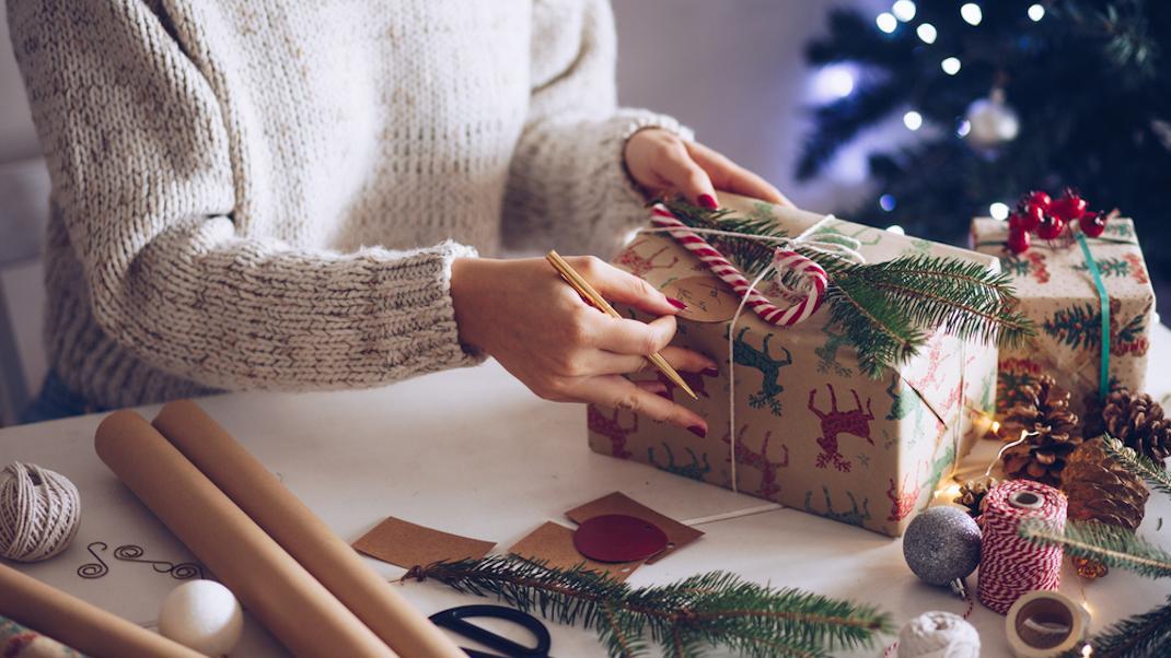 Γυναίκα τυλίγει χριστουγεννιάτικα δώρα