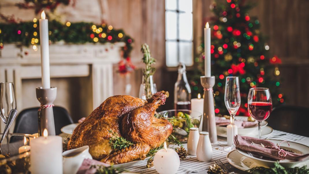 Εορταστικό τραπέζι με γαλοπούλα και χριστουγεννιάτικο δέντρο στο background